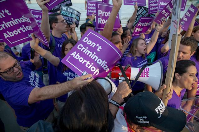 <p>Pro-choice and anti-abortion protesters demonstrate in front of the U.S. Supreme Court on July 9, 2018 in Washington, D.C. President Donald Trump is set to announce his Supreme Court pick Monday night. (Photo: Tasos Katopodis/Getty Images) </p>