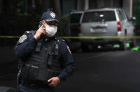 An abandoned vehicle that is believed to have been used by gunmen in an attack against the chief of police is sealed off with yellow tape and guarded by police, in Mexico City, Friday, June 26, 2020. Heavily armed gunmen attacked and wounded Omar Garcia Harfuch in a brazen operation that left an unspecified number of dead, Mayor Claudia Sheinbaum said Friday. (AP Photo/Marco Ugarte)