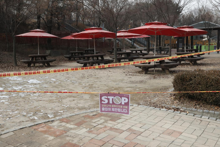 """A part of park is taped off with a sign which reads """"Access restrictions to prevent the spread of COVID-19"""" for the social distancing measures and a precaution against the coronavirus at a park in Seoul, South Korea, Wednesday, Dec. 23, 2020. South Korea has added more than 1,000 new coronavirus cases in a resurgence that is erasing hard-won epidemiological gains and eroding public confidence in the government's ability to handle the outbreak. (AP Photo/Lee Jin-man)"""