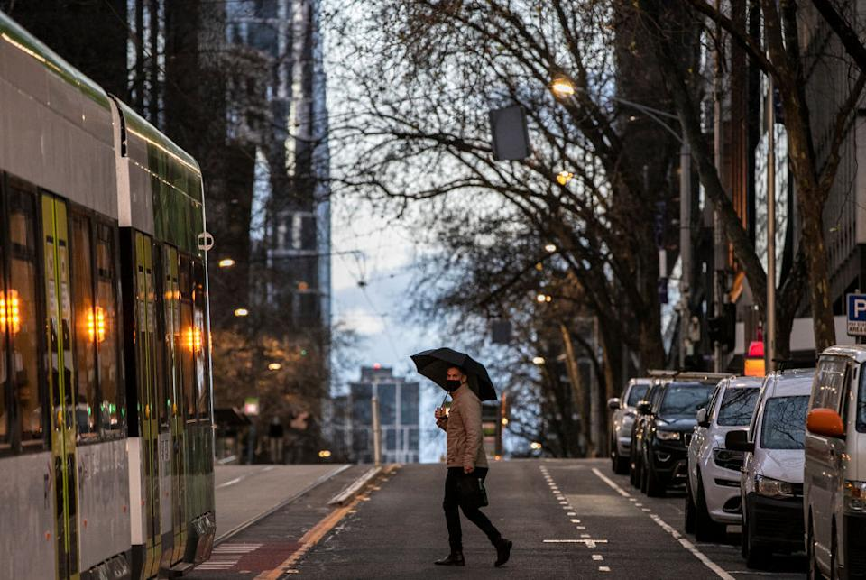 A man is seen wearing a face mask while crossing Bourke Street in Melbourne, Australia.