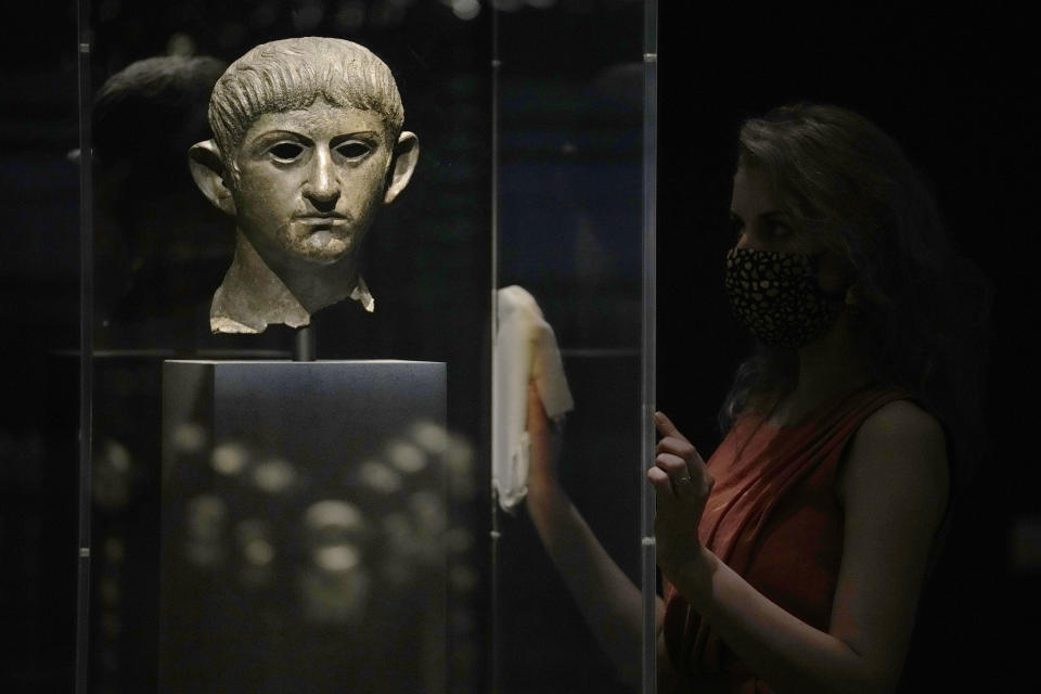 """A museum employee poses for photographers next to a bronze head of Roman emperor Nero dating from around AD 54-61 and found in the River Alde at Rendham in Suffolk, eastern England, during a media preview for the """"Nero: the man behind the myth"""" exhibition, at the British Museum in London, Monday, May 24, 2021. The exhibition, which opens to visitors on May 27 and runs until October 24, explores the true story of Rome's fifth emperor informed by new research and archaeological evidence from the time. (AP Photo/Matt Dunham)"""