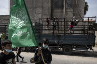 Palestinian children swing on the back of a truck as Hamas supporters attend a protest in solidarity with Muslim worshippers in Jerusalem, in Gaza City, Friday, April. 23, 2021. (AP Photo/Khalil Hamra)