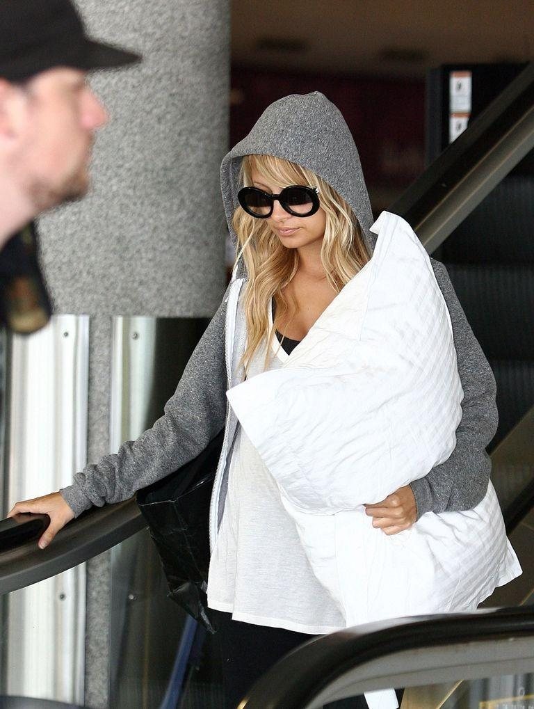 <p>Nicole Richie keeps things (very) casual in a white t-shirt and grey hoodie as she arrives at Perth Airport in 2007. </p>