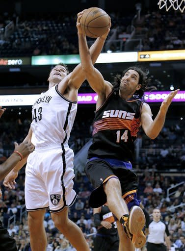 Brooklyn Nets' Kris Humphries (43) and Phoenix Suns' Luis Scola (14), of Argentina, battle for a rebound during the first half of an NBA basketball game, Sunday, March 24, 2013, in Phoenix. (AP Photo/Matt York)