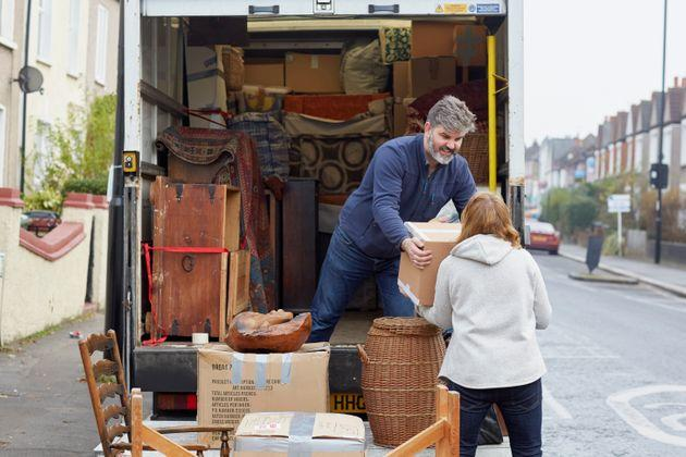 A man and a woman load a moving truck with furniture.