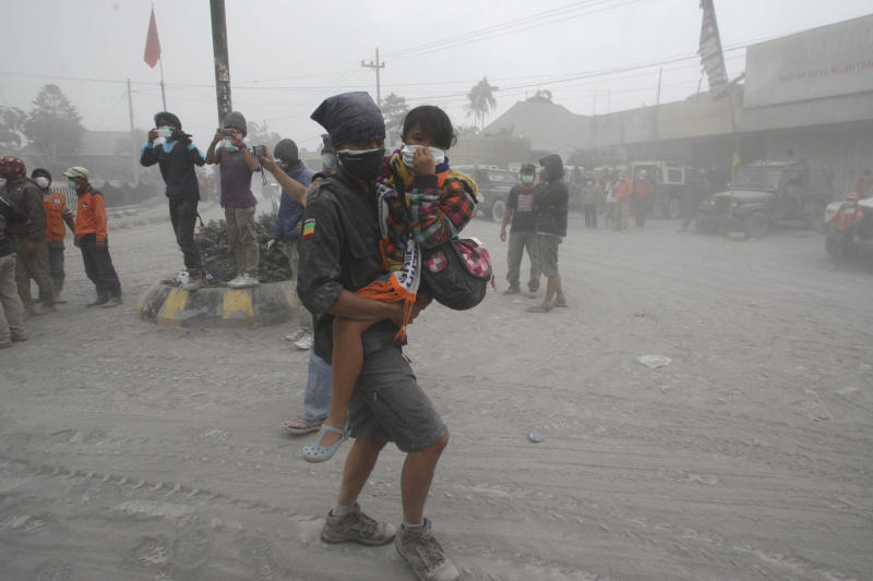 A rescuer carries a child to a truck for evacuation following an eruption of Mount Kelud, in Malang, East Java, Indonesia, Saturday, Feb. 15, 2014. The powerful volcanic eruption on Indonesia's most populous island blasted ash and debris 18 kilometers (12 miles) into the air Friday, forcing authorities to evacuate more than 100,000 and close seven airports. (AP Photo/Trisnadi)