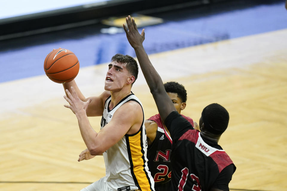 Iowa center Luka Garza, left, drives to the basket past Northern Illinois center Adong Makuoi, right, during the first half of an NCAA college basketball game, Sunday, Dec. 13, 2020, in Iowa City, Iowa. (AP Photo/Charlie Neibergall)