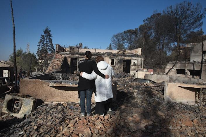 Israeli settlers grieve over their burnt houses in the Halamish settlement, also known as Neveh Tzuf, in the occupied West Bank on November 27, 2016, after 45 homes were damaged or completely destroyed by fire (AFP Photo/Menahem Kahana)