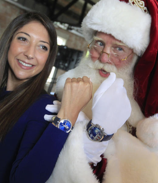 "Brady White portrays Santa Clause, right, as he and model Marisa Neira show off his and hers ""Poetic Wish"" watches from Van Cleef & Arpels during the unveiling of the Neiman Marcus 2012 Christmas Book in Dallas, Tuesday, Oct. 9, 2012. The Van Cleef & Arpels watches include a trip to Paris and Geneva that is priced for sale at $1,090,000. (AP Photo/LM Otero)"
