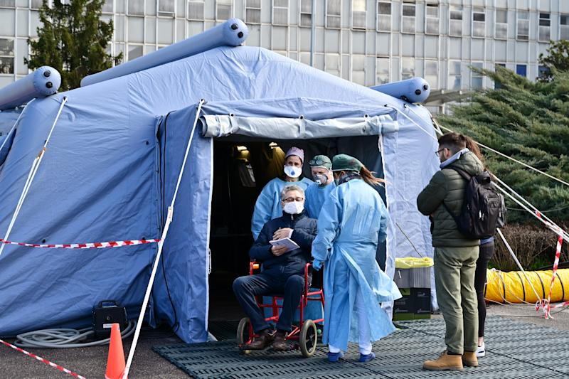 A man receives assistance in the a pre-triage medical tent in front of the Cremona hospital, in Cremona, northern Italy, on March 4, 2020. - Italy will recommend people stop kissing in public, avoid shaking hands and keep a safe distance from each other to limit the spread of the novel coronavirus. Other measures to be approved by the government, which has borne the brunt of the COVID-19 disease, includes a plan to play all football matches behind closed doors. (Photo by MIGUEL MEDINA / AFP) (Photo by MIGUEL MEDINA/AFP via Getty Images)