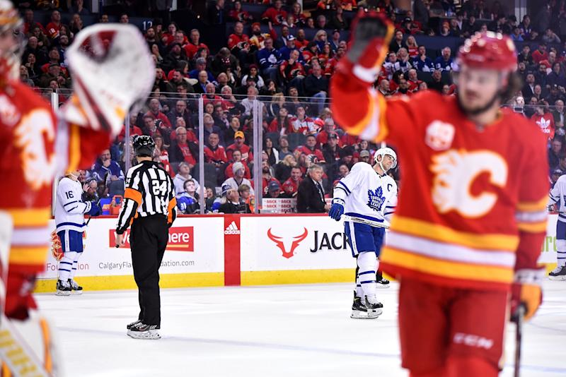 CALGARY, AB - DECEMBER 12: Toronto Maple Leafs Center John Tavares (91) looks on as Calgary Flames Goalie David Rittich (33) gets a high five from Calgary Flames Defenceman Rasmus Andersson (4) following a save during the third period of an NHL game where the Calgary Flames hosted the Toronto Maple Leafs on December 12, 2019, at the Scotiabank Saddledome in Calgary, AB. (Photo by Brett Holmes/Icon Sportswire via Getty Images)