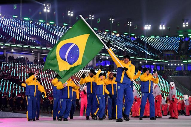 <p>Flag bearer Edson Bindilatti of Brazil and teammates enter the stadium wearing yellow-and-blue color-block puffer jackets and pants during the opening ceremony of the 2018 PyeongChang Games. (Photo: Matthias Hangst/Getty Images) </p>
