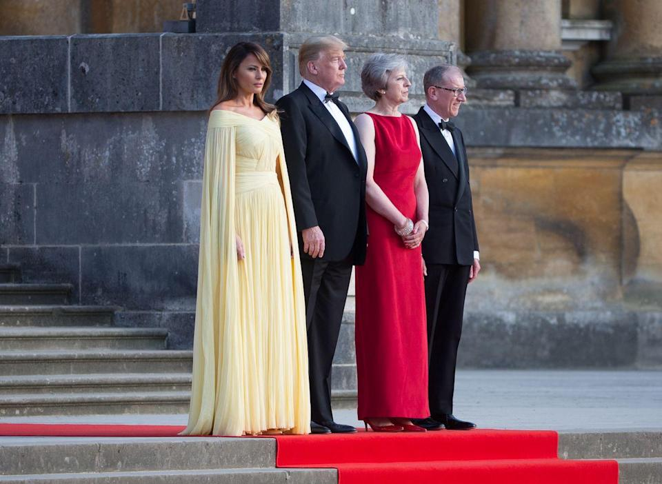 For a dinner with Theresa May at Blenhiem Palace, Melania turned heads in a stunning lemon yellow J.Mendel gown costing £5000. [Photo: Rex]