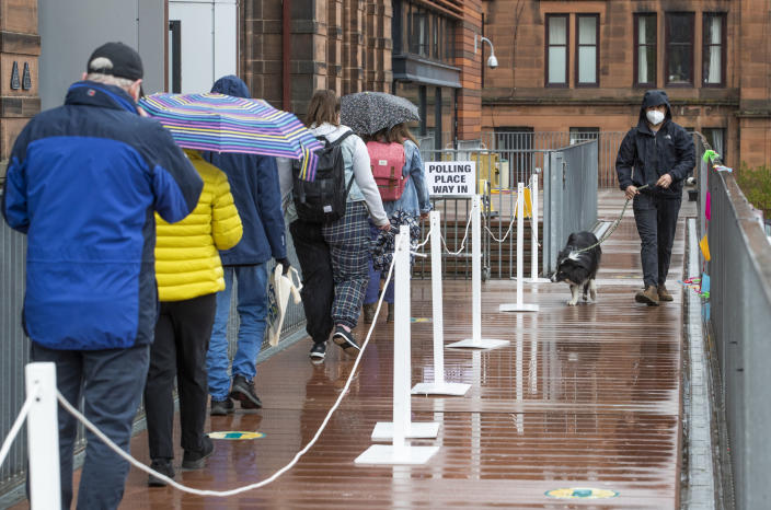 People queue to vote outside a polling station in Glasgow, Scotland, Thursday May 6, 2021. Scots are heading to the polls to elect the next Scottish Government - though the coronavirus pandemic means it could be more than 48 hours before all the results are counted. (Jane Barlow/PA via AP)