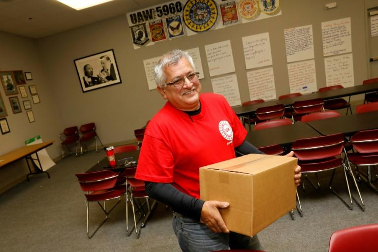 Louis Rocha, president of the UAW Local 5960, carries a box of food supplies for a striking worker on October 11 in Lake Orion, Michigan (AFP Photo/JEFF KOWALSKY)