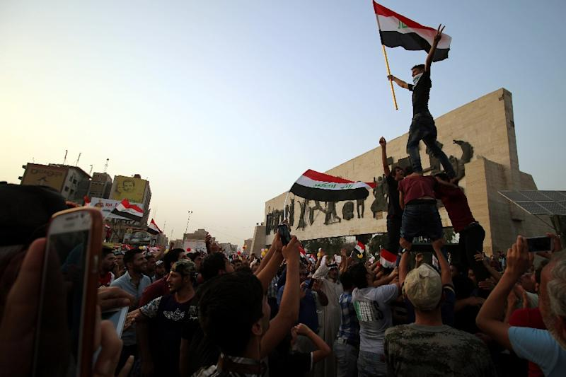 Iraqi men wave their national flag during a demonstration against corruption and poor services in Baghdad on August 7, 2015 (AFP Photo/Haidar Mohammed Ali)