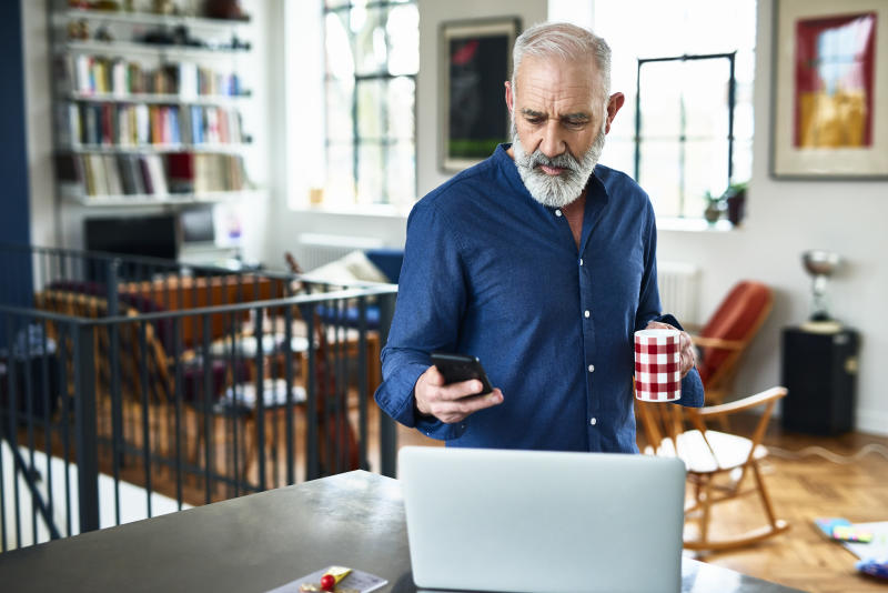 Man in his 50s in apartment, texting, with laptop on work surface, serious expression on face, planning for the day ahead, drinking coffee