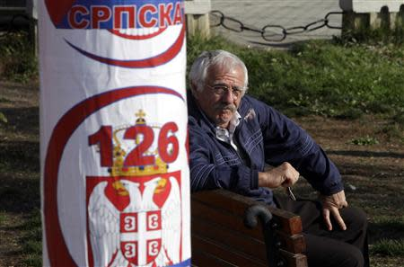 "A Kosovar Serb sits near a poster of the ""Gradanska inicijativa Srbija"" (Serbian Citizens' Initiative) political party in the town of Gracanica, which is inhabited by a Serbian minority, November 2, 2013. REUTERS/Hazir Reka"
