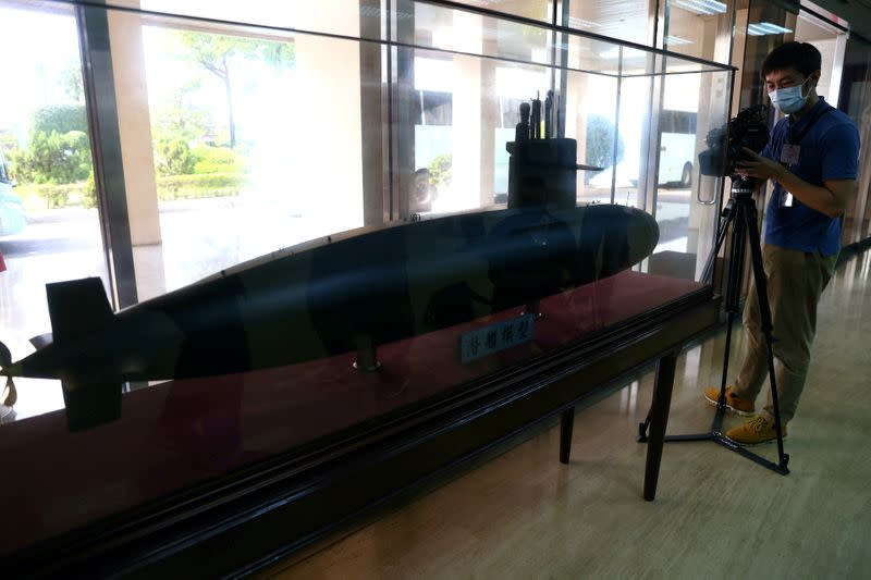 FILE PHOTO: A member of the media takes photos of a Submarine model at the lobby of CSBC Corporation office building in Kaohsiung