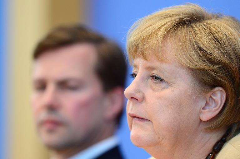 German chancellor Angela Merkel (R) sits next to her spokesman Steffen Seibert as she gives a press conference on September 17, 2012 in Berlin