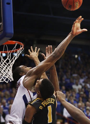 Kansas forward Thomas Robinson, left, blocks a shot by Missouri guard Phil Pressey (1) at the end of regulation time during an NCAA college basketball game in Lawrence, Kan., Saturday, Feb. 25, 2012. The blocked shot sent the game into overtime. Kansas defeated Missouri 87-86 in overtime.(AP Photo/Orlin Wagner)
