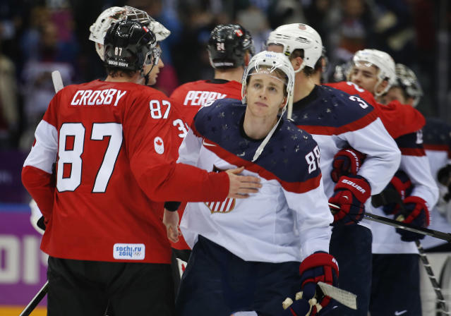 Canada forward Sidney Crosby consoles USA forward Patrick Kane after Canada won 1-0 in a men's semifinal ice hockey game at the 2014 Winter Olympics, Friday, Feb. 21, 2014, in Sochi, Russia. (AP Photo/Julio Cortez)