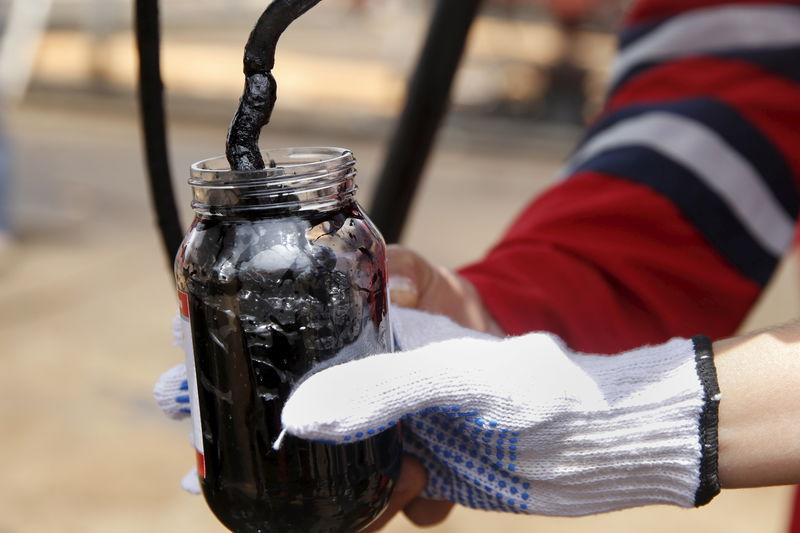 Oilfield workers collect a crude oil sample at an oil well operated by Venezuela's state oil company PDVSA, in the oil rich Orinoco belt, near Morichal at the state of Monagas