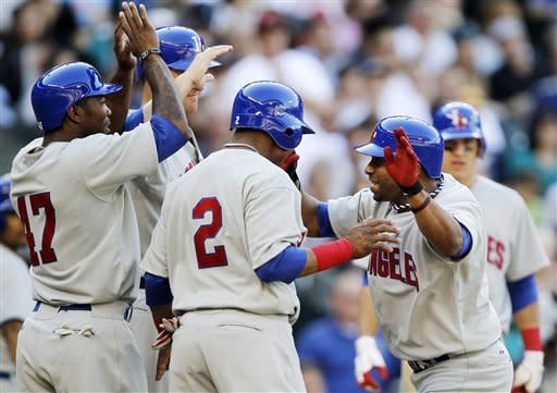 Los Angeles Angels' Alberto Callaspo, right, is greeted at home by Howard Kendrick (47), Mark Trumbo and Erick Aybar (2) after his sixth-inning grand slam against the Seattle Mariners in a baseball game, Saturday, May 26, 2012, in Seattle. (AP Photo/Elaine Thompson)