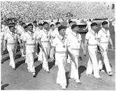 <p>American athletes wear berets and knit sweaters as they lead the opening ceremony as the host country. The 1932 Summer Olympic Games in Los Angeles marked the first time the West Coast city would host the games. </p>