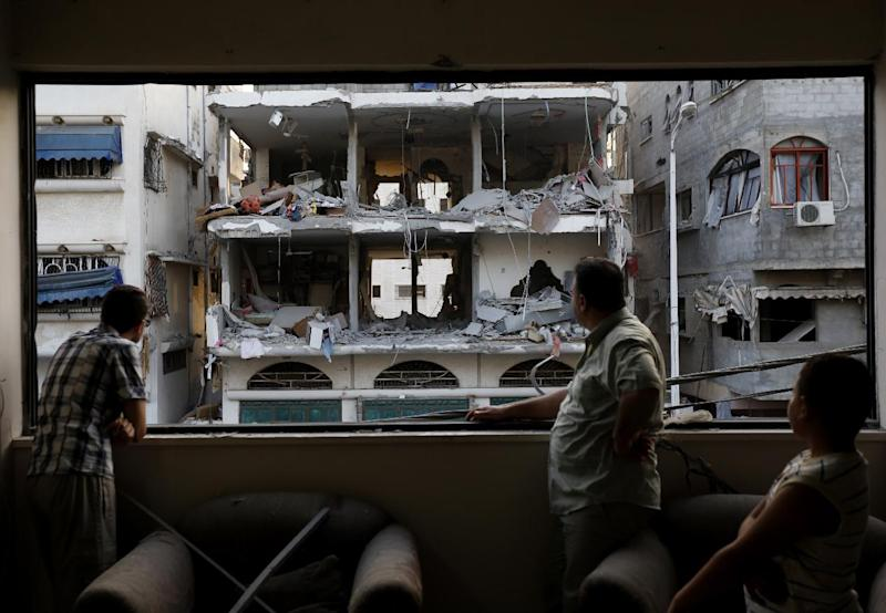 A Palestinian man and his sons stand at their damaged living room as they look outside at a neighboring building which was targeted in an Israeli military strike in Gaza City on July 12, 2014