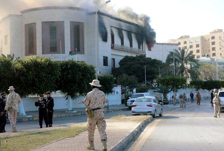 FILE PHOTO: Security forces stand at the site of the headquarters of Libya's foreign ministry after a suicide attack in Tripoli