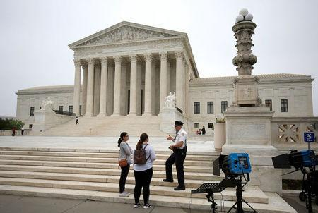 A police officer speaks with tourists before a decision was released allowing the legalization of sports betting at the Supreme Court in Washington, U.S., May 14, 2018. REUTERS/Joshua Roberts