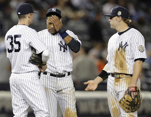 New York Yankees shortstop Brendan Ryan (35), second baseman Robinson Cano and first baseman Mark Reynolds wait during a pitching change after reliever David Huff gave up a sixth-inning, three-run home run to Tampa Bay Rays Evan Longoria in a baseball game, Wednesday, Sept. 25, 2013, in New York. (AP Photo/Kathy Willens)