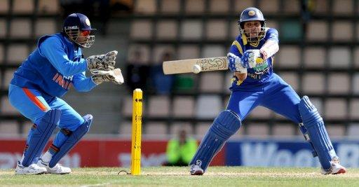Sri Lankan batsman Tillakaratne Dilshan (right) cuts a ball towards the boundary on the way to scoring his century as India's wicketkeeper MS Dhoni looks on in their ODI in Hobart on Tuesday. Dilshan equalled his best one-day score of 160, but India's Virat Kohli blasted an unbeaten 133 off just 86 balls as India's seven-wicket bonus point victory over Sri Lanka kept them alive in the series