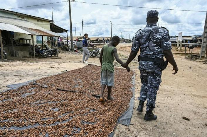 A police officer with a child who was drying cocoa in the sun