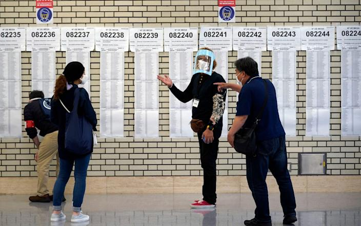 Peruvian nationals living in Japan gather before voters lists at a polling station in Tokyo, Japan, - Shutterstock
