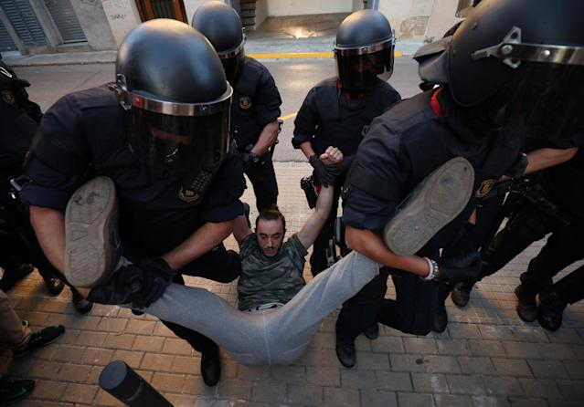 <p>Catalan police officers remove a protestor from the street outside a Unipost office which was raided in search of material for the proposed October 1 referendum, in Terrassa, Spain, Sept. 19, 2017. (Photo: Albert Gea/Reuters) </p>