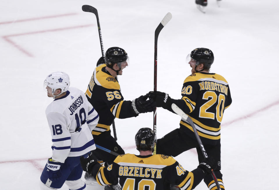 Boston Bruins center Joakim Nordstrom (20) is congratulated by Noel Acciari (55) after his goal against the Toronto Maple Leafs during the first period of Game 7 of an NHL hockey first-round playoff series, Tuesday, April 23, 2019, in Boston. At left is Toronto Maple Leafs left wing Andreas Johnsson (18), in foreground is Boston Bruins defenseman Matt Grzelcyk (48). (AP Photo/Charles Krupa)