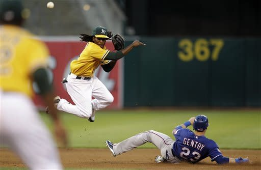 Oakland Athletics second baseman Jemile Weeks, left, throws over Texas Rangers' Craig Gentry (23) to complete a double play in the fourth inning of a baseball game, Tuesday, July 17, 2012, in Oakland, Calif. Rangers' Ian Kinsler was out at first base. (AP Photo/Ben Margot)