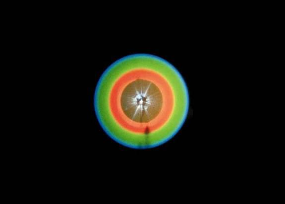 This pattern is created when scientists send a laser beam through a crystal, occasionally producing a connected pair of twin photos. These photons will always be separated from each other by 180 around the circle.