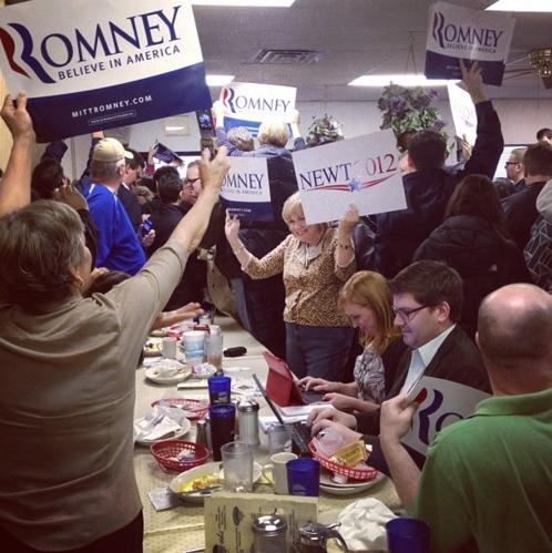 """I can't decide!"" a woman says as she waves both Romney and Newt signs this morning at Tommy's."