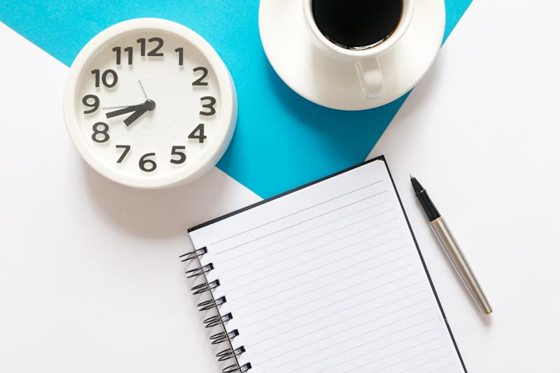 Flat lay of Alarm clock, coffee, notebook and pen on blue and white background