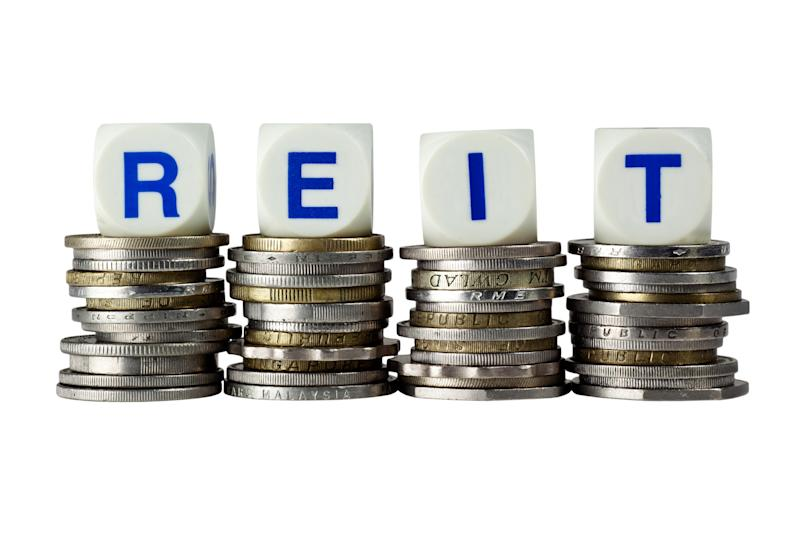 The acronym REIT spelled out with dice sitting atop piles of coins