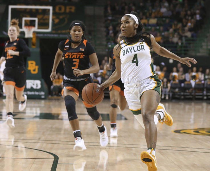 CORRECTS DATE Baylor guard Te'a Cooper drives to the basket past Oklahoma State guard Micah Dennis, left, on a fast break in the first half of an NCAA college basketball game, Sunday, Jan. 12, 2020, in Waco, Texas. (Rod Aydelotte/Waco Tribune Herald via AP)