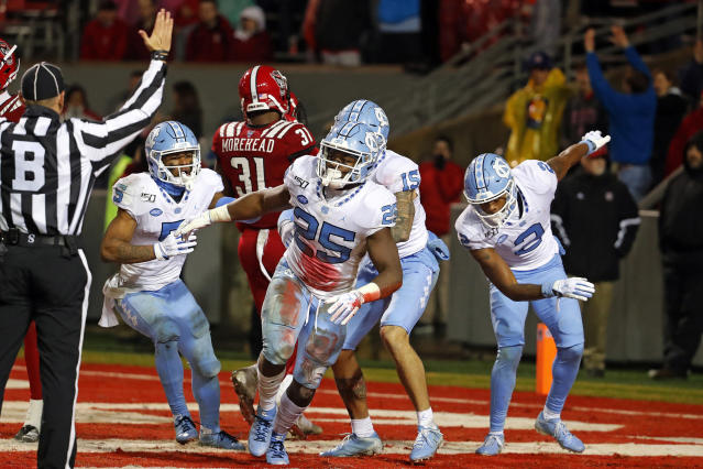 North Carolina's Javonte Williams (25) celebrates a touchdown against North Carolina State with teammates during the second half of an NCAA college football game in Raleigh, N.C., Saturday, Nov. 30, 2019. (AP Photo/Karl B DeBlaker)