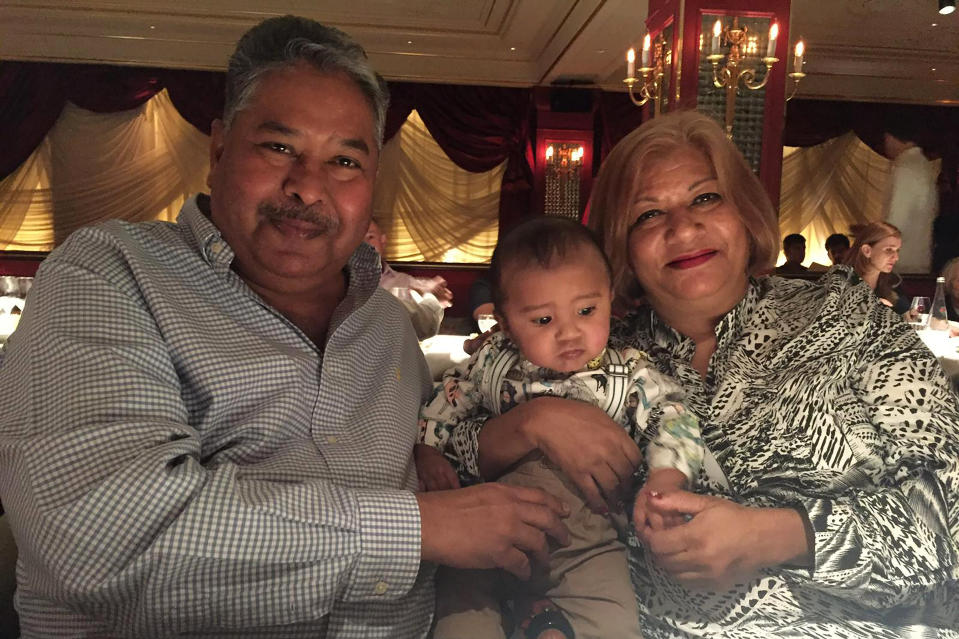 In this undated photo provided by Amrohi family, Yamini Amrohi, right, poses with her grandson and late husband Ashok Amrohi, who died of COVID-19, at a restaurant in London. Ashok, a medical doctor before joining the diplomatic corps, had traveled the world. He'd been ambassador to Algeria, Mozambique and Brunei, and had retired to Gurgaon, a city just outside the capital, and a life of golf and piano lessons. (Amrohi family via AP)