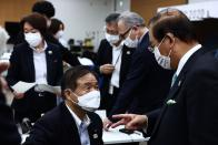 Tokyo 2020 organising committee vice-president Toshiaki Endo, second left, speaks with Tokyo 2020 CEO Toshiro Muto after the five-party meeting in Tokyo, Thursday, July 8, 2021. (Behrouz Mehri/Pool Photo via AP)