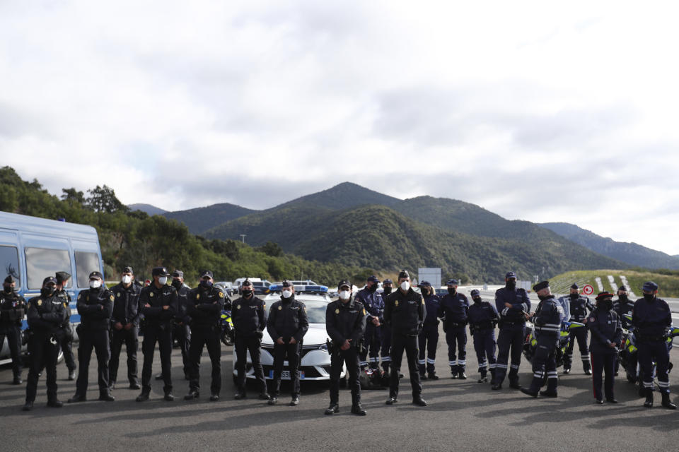 French police officers stand in line as French President Emmanuel Macron holds a visit on the strengthening border controls at the crossing between Spain and France, at Le Perthus, France, Thursday, Nov. 5, 2020. (Guillaume Horcajuelo, Pool via AP)