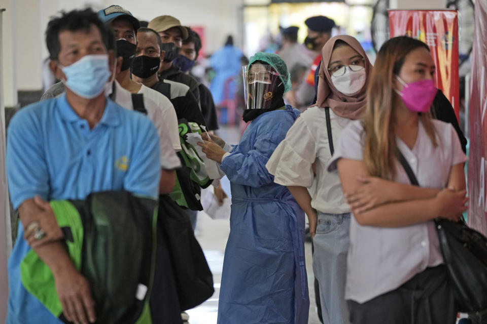A medical worker in protective gear checks the paperwork of people getting the Sinovac COVID-19 vaccine during a mass vaccination in Depok on the outskirts of Jakarta, Indonesia, Friday, June 25, 2021. The world's fourth most populous country, has seen COVID-19 infections surge in recent weeks, putting pressure on hospitals, including in the capital city, where most of hospital beds are full, and has added urgency to the government's plan to inoculate 1 million people each day by next month. (AP Photo/Dita Alangkara)