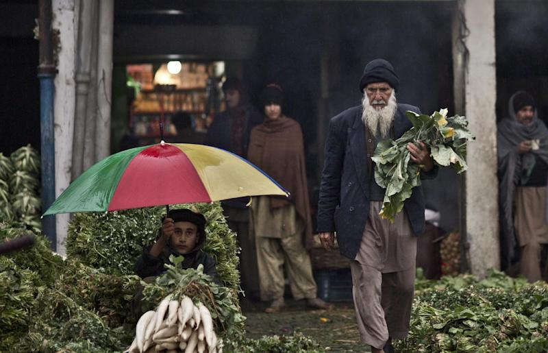 An elderly Pakistani man, collects vegetables left on the ground by vendors at a wholesale market on the outskirts of Islamabad, Pakistan, Thursday, Feb. 6, 2014. (AP Photo/Muhammed Muheisen)